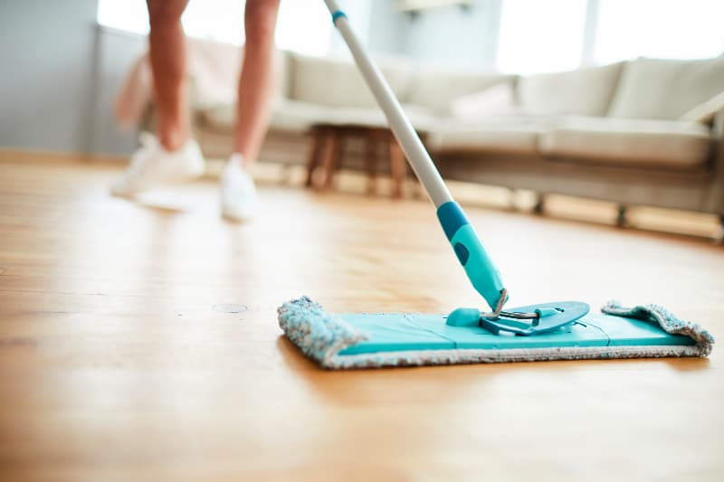 Woman demonstrating how to clean wood floors with a dry microfiber mop