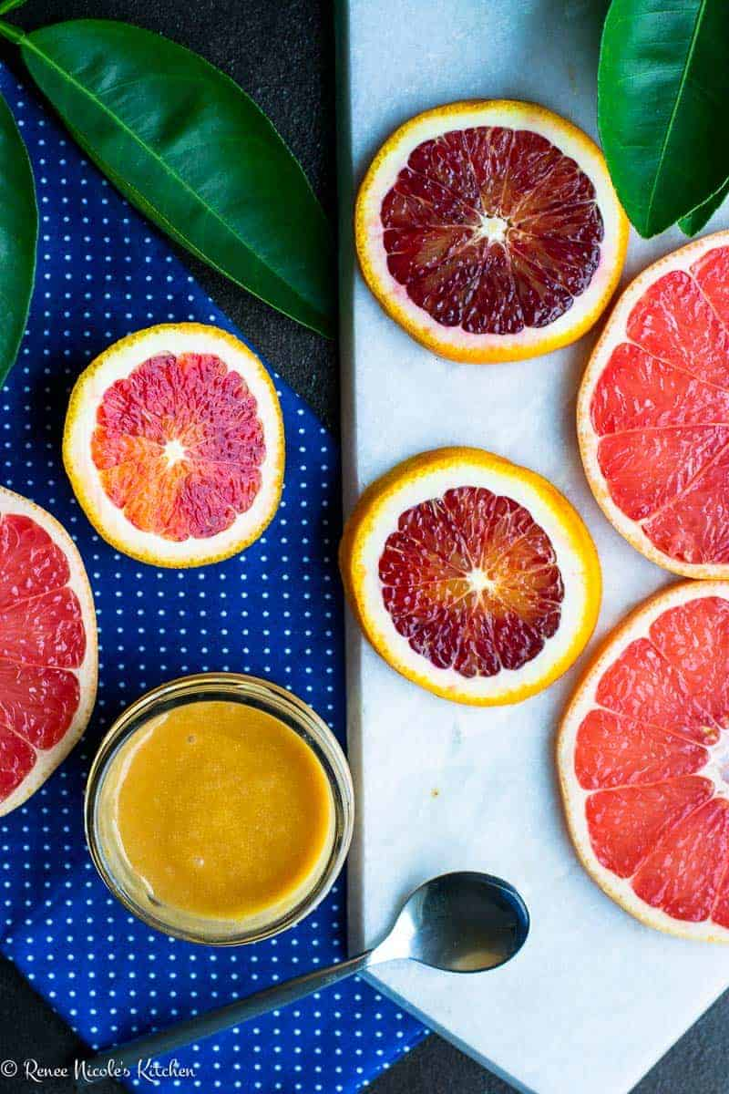 Overhead shot of grapefruit and blood orange curd in a glass jar next to slices of fresh grapefruit and blood orange on a blue and white background.