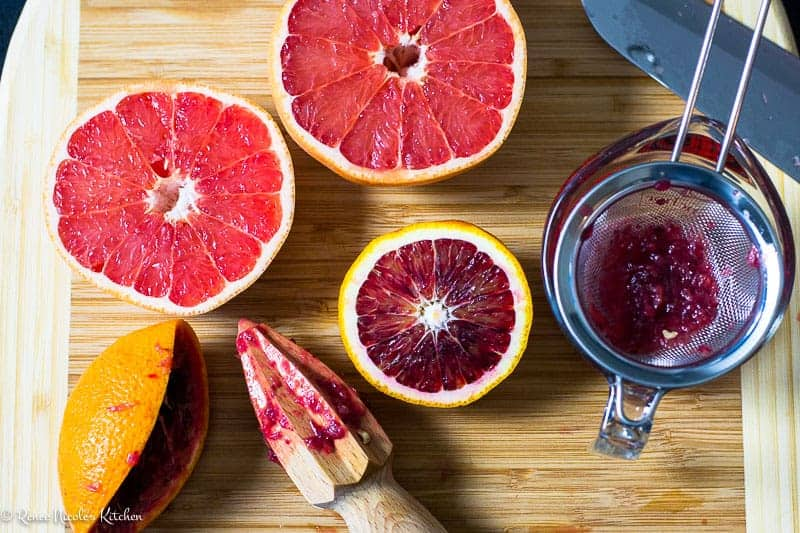 Grapefruit and blood orange sliced in half on a cutting board. half of the blood orange has been juiced into a strainer with a citrus juicer.