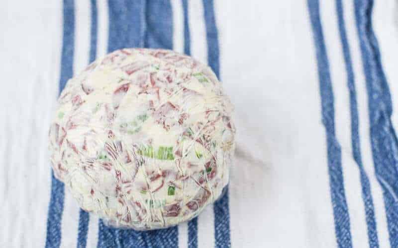 dried beef cheese ball, cream cheese ball with green onions and dried beef in saran wrap on blue and white striped tea towel