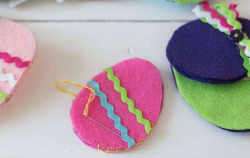 Another view of Bright pink felt Easter egg with ricrac sewing together using a blanket stitch