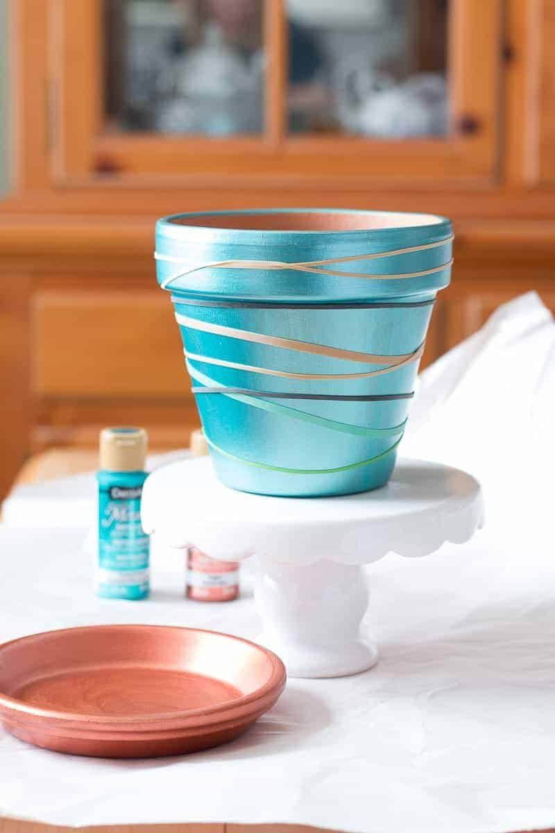 Painted clay pot with rubber bands for adding design
