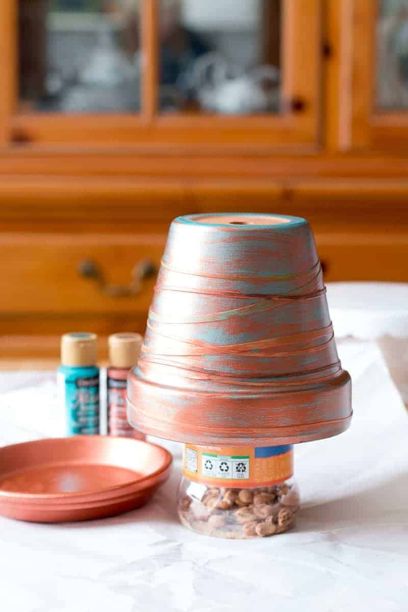 One coat of copper paint on clay pot with rubber bands