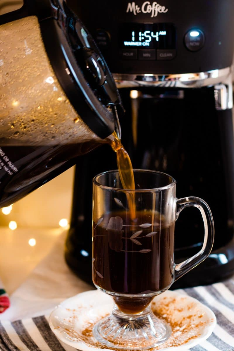 Fresh coffee being poured from a Mr. Coffee glass carafe into a glass mug