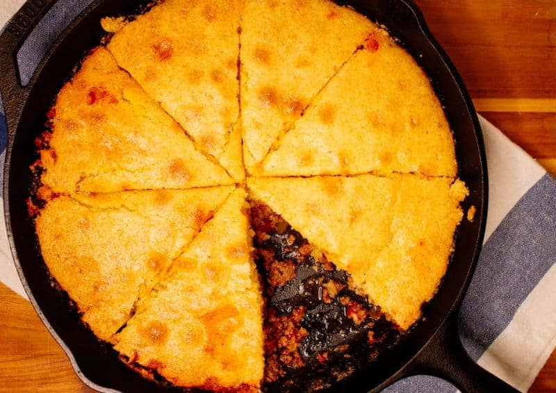Beef Tamale Pie topped with cornbread in a cast iron skillet fresh out of the oven