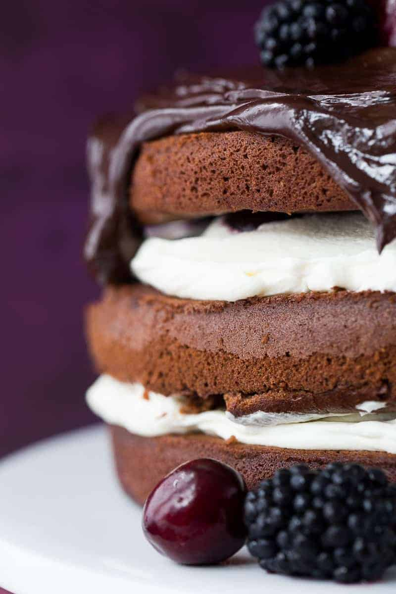 Side view of 3 chocolate sponges stacked on top of each other with whipped cream in between each layer and a dark chocolate ganache over the top and dripping down the sides.