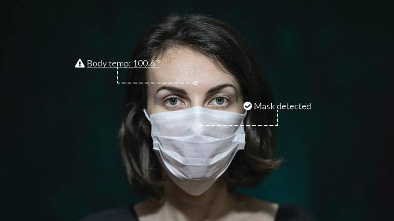 Woman wearing a medical mask covering her mouth and nose that has been scanned by a temperature sensing facial recognition camera; her body temp (100.6 degrees) is displayed, as is a note that a mask as been detected.