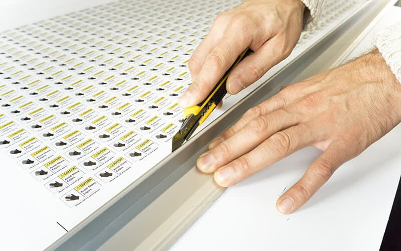 A Sheet Of Stickers Being Cut