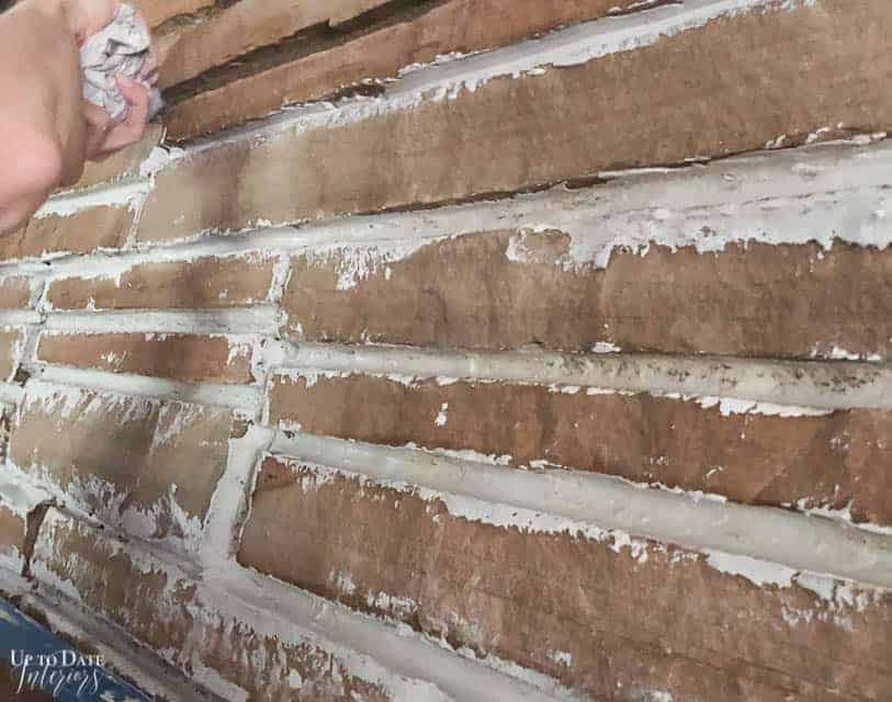 Applying a german smear technique with joint compound on a stone fireplace.