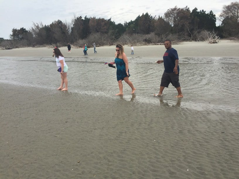 People exploring the shore and walking into the water. Best time to see dolphins in Charleston, SC