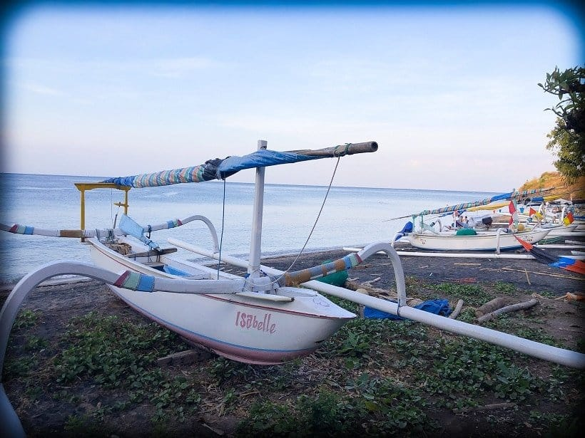 A traditional Balinese fishing boat with bamboo outriggers sits on the beach in Amed Bali