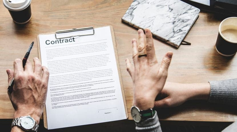 hands over a contract