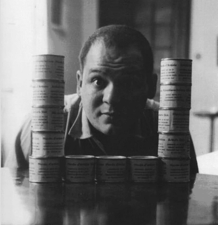 Piero Manzoni posing with his artwork