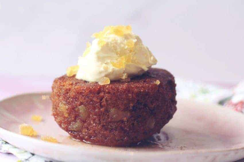 Side view of an individual sticky ginger cake topped with clotted cream and crystallised ginger