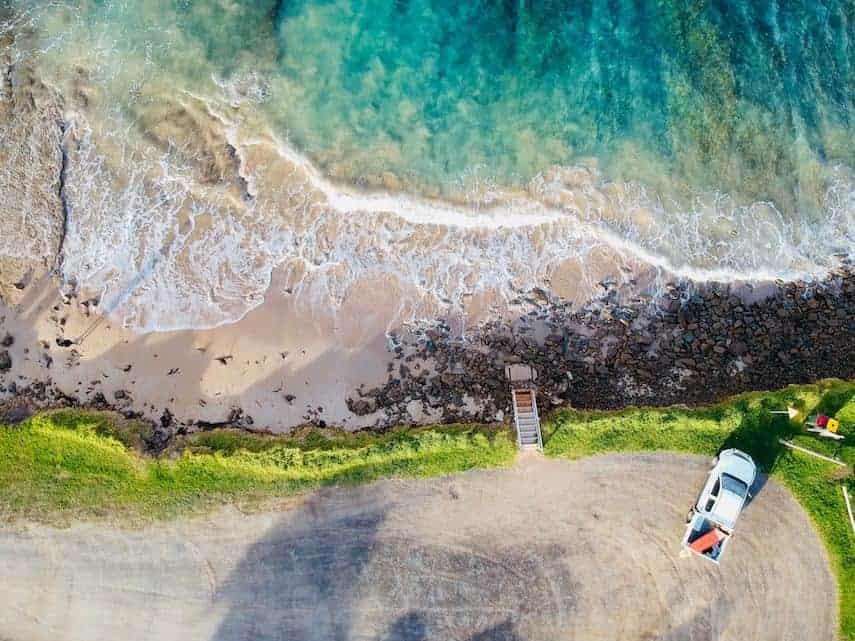 Aerial shot of the ocean with a rocky shoreline and pick up truck parked in the car park above the shore