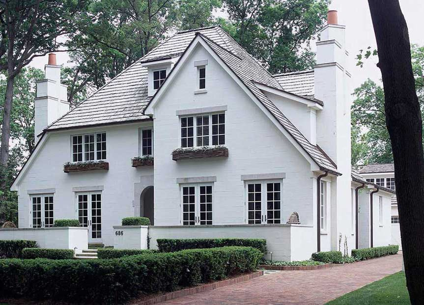 a traditional home exterior design with cinder block walls painted in white