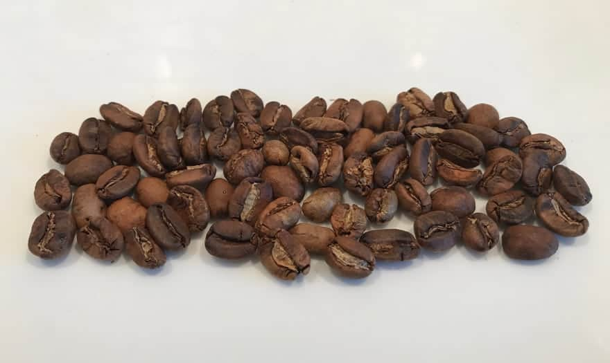 Blonde roast coffee beans on a white plate