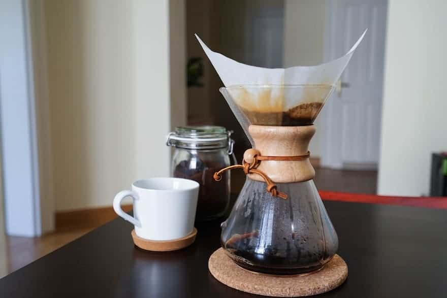 Chemex coffee brewer sitting on a table with a white coffee mug