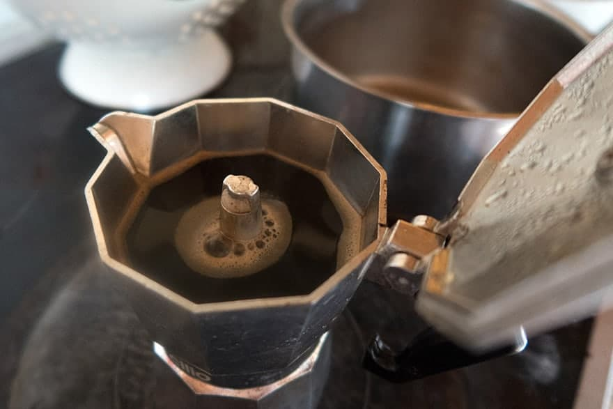 A moka pot fills with coffee on the stove