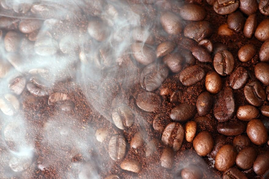 Smoke rises from freshly roasted coffee beans