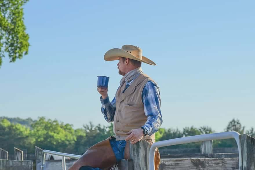cowboy drinking coffee from a metal cup with one leg swung over the rail of a corral