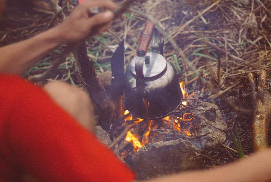 A camper hangs a metal kettle over a campfire