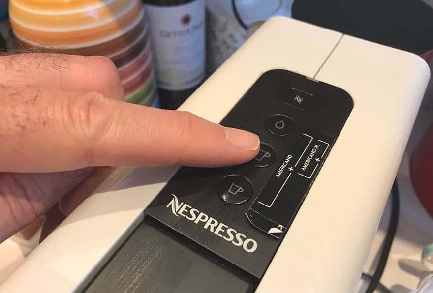 Finger on the lungo button of a Nespresso Essenza Mini