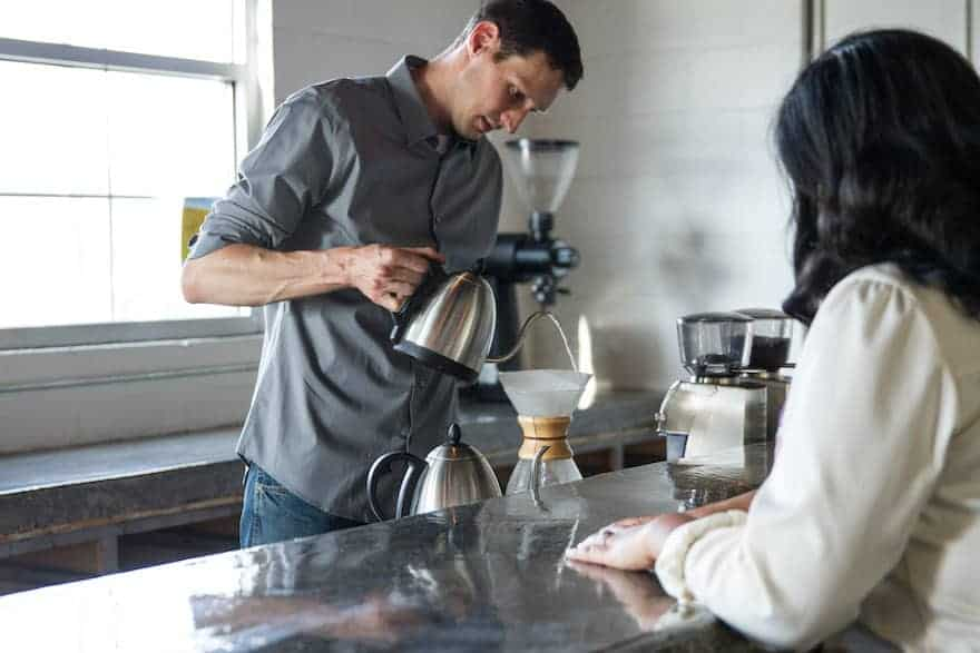 Phil Cook prepares pour-over coffee using a Chemex