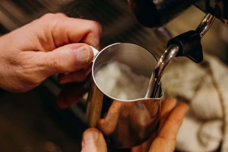 Hands frothing milk for coffee