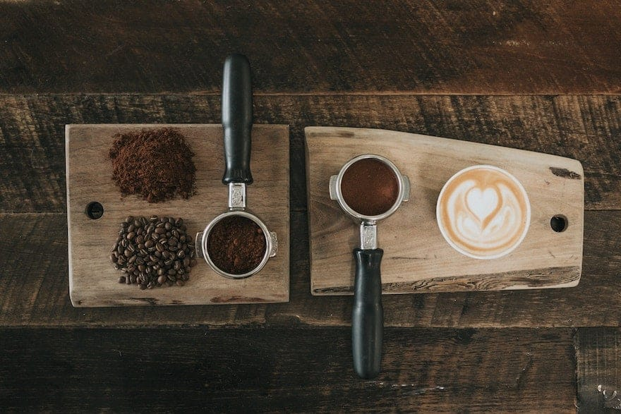 Coffee beans and portafilters on a cutting board