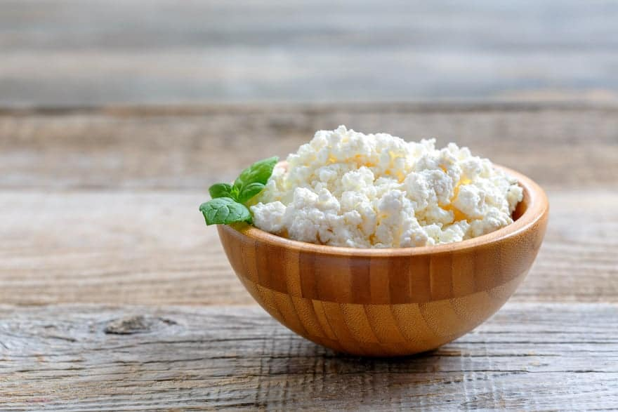 Cottage cheese in a wooden bowl on a wooden table