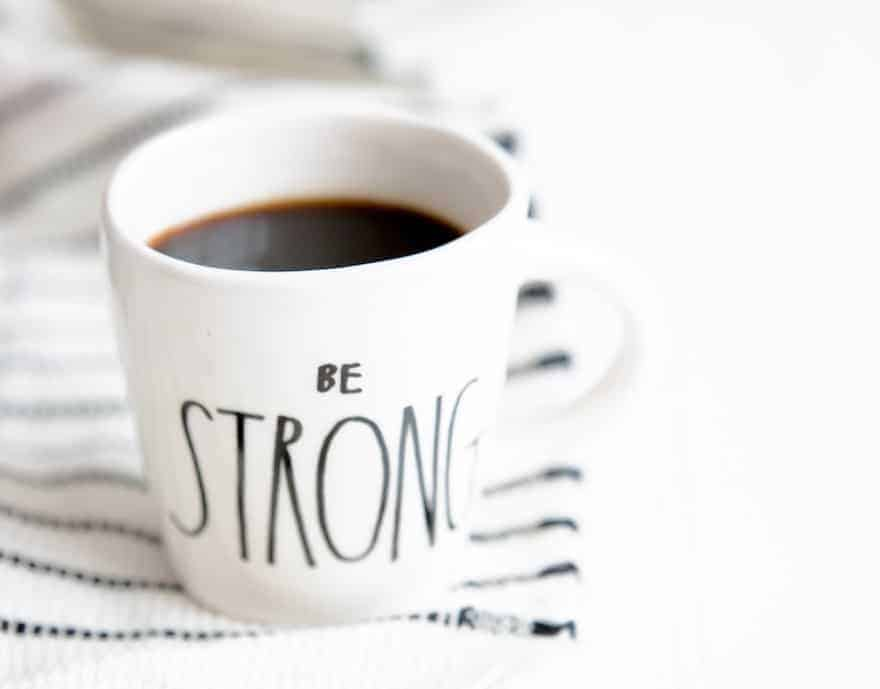 A white coffee mug with the words Be Strong written on the outside