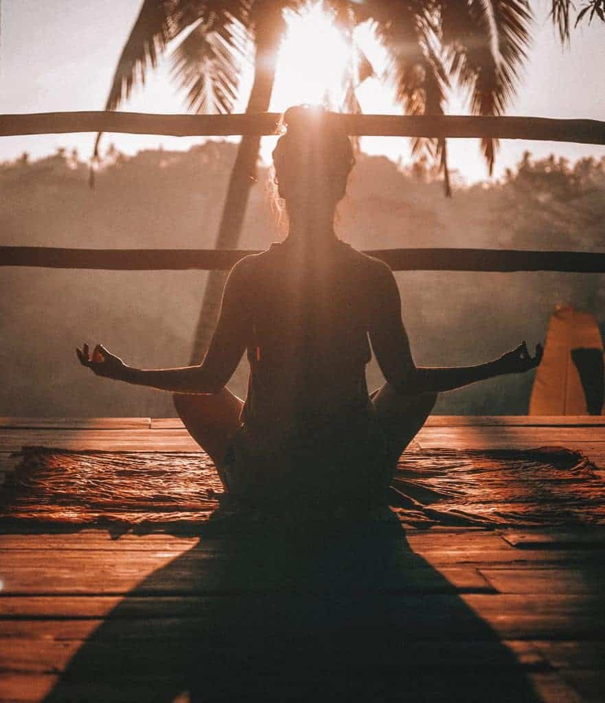Woman meditating under palm tree in the setting sun