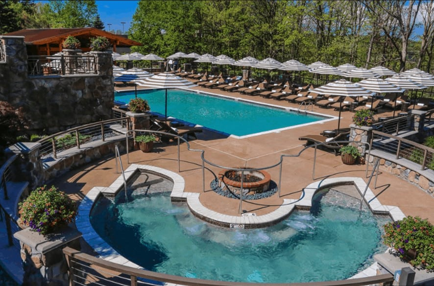 The adult pool, large hot tub and loung chairs with umbrellas at nemacolin woodlands