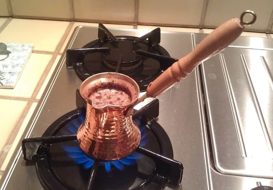 Turkish coffee foaming in a Cezve on the stove