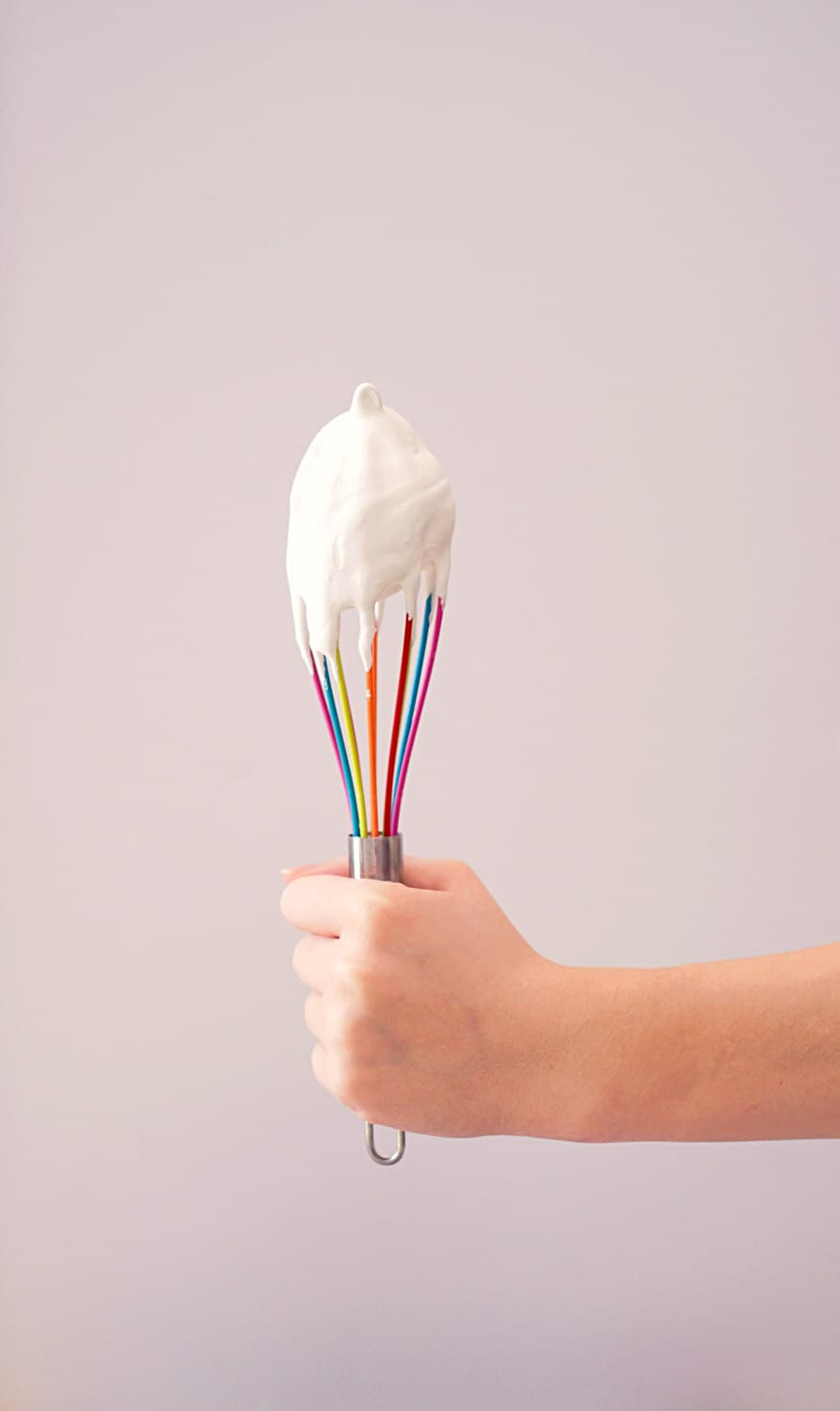 A hand holding a whisk covered in buttercream icing.