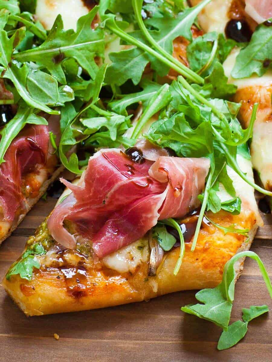 prosciutto on top of basil pesto and arugula pizza