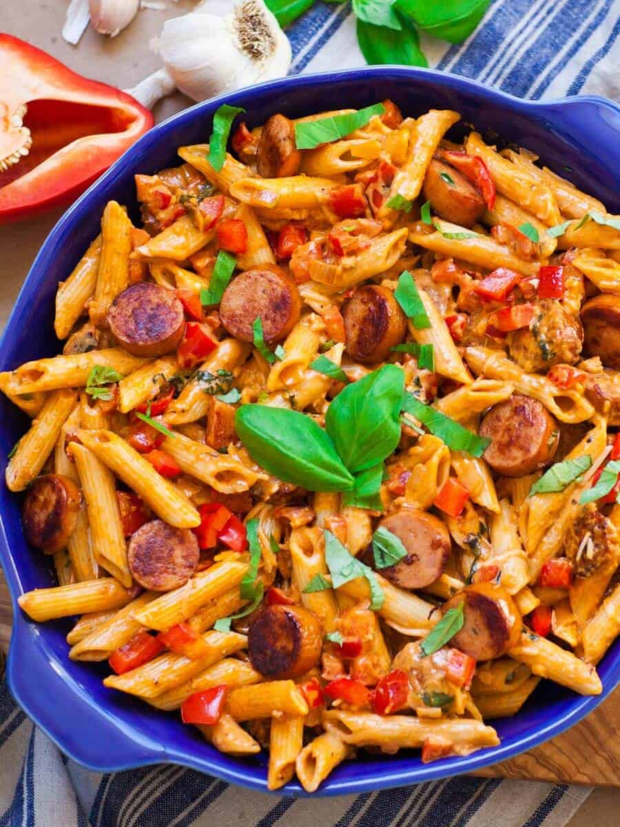 smoky sausage pasta in blue dish, with peppers and fresh basil