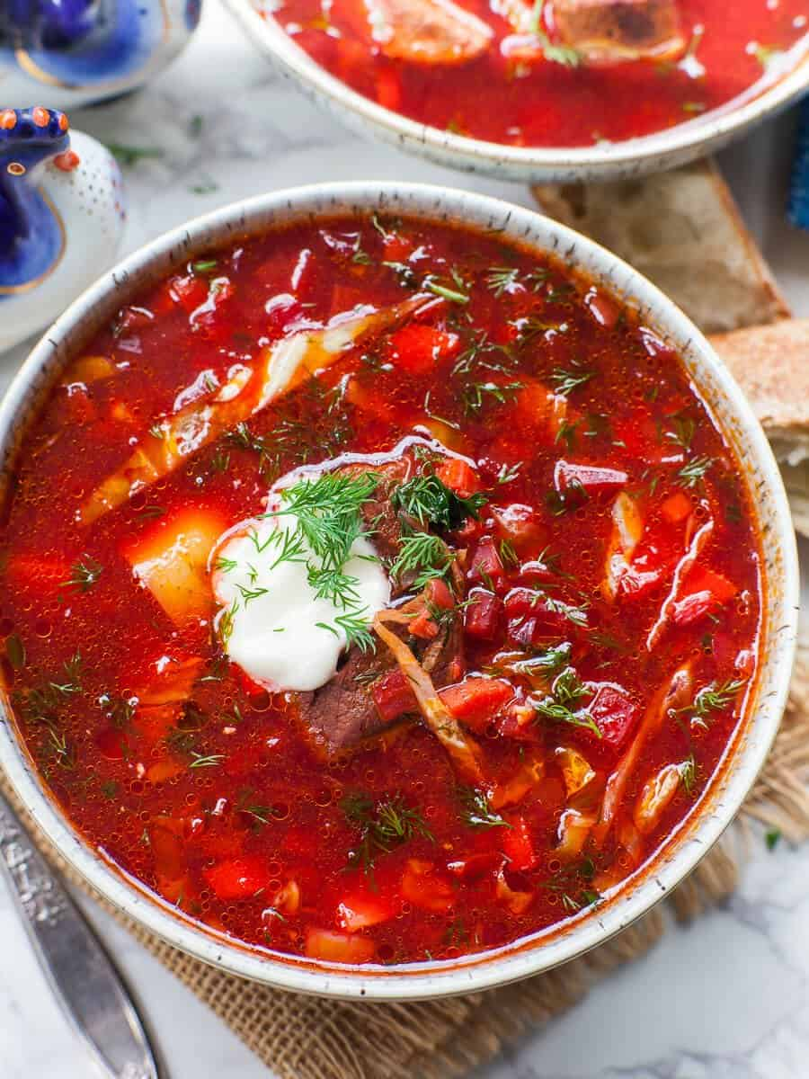 close up of classic beef borscht in bowl with sour cream and fresh dill