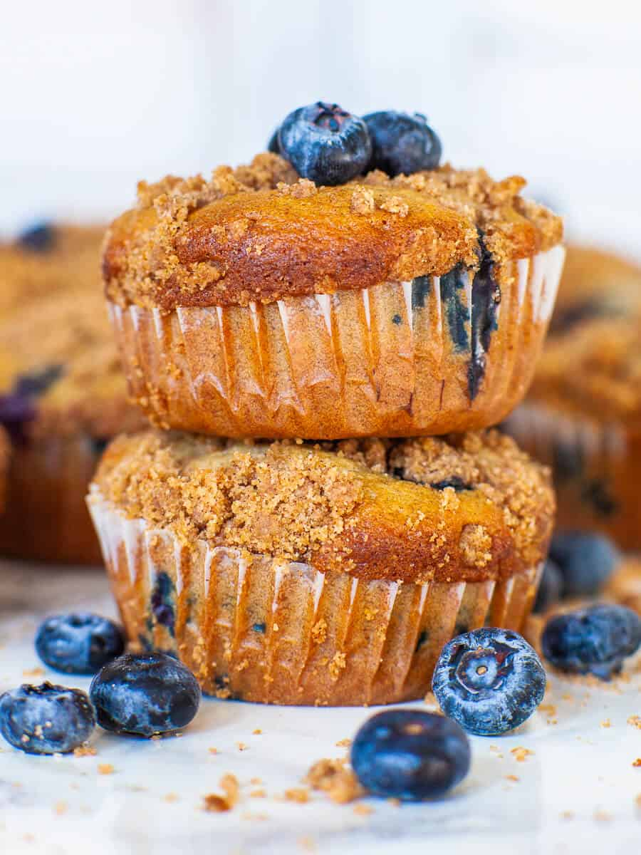 stacked blueberry muffins with fresh berries and cinnamon crumble