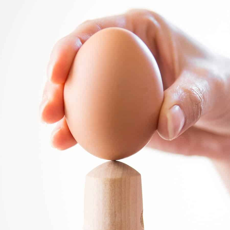 Crack the blunt bottom of the egg on a curved object before boiling.