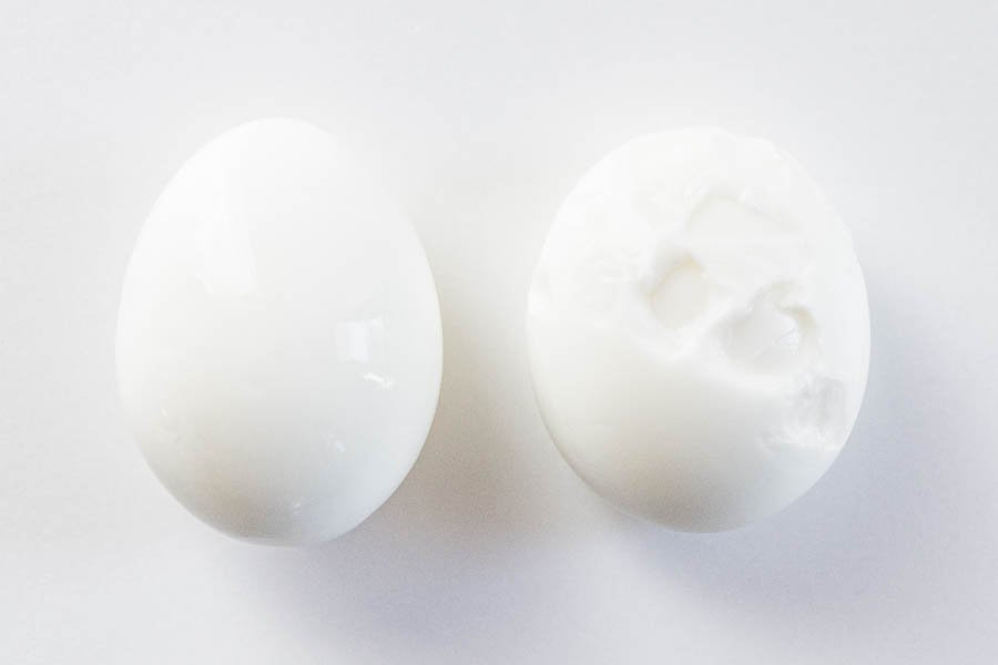 Perfectly peeled boiled egg on the left using my trick, damaged boiled egg on the right.