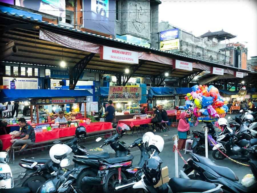 Food stalls with motorcycles parked in front at a Bali night market in Gianyar, Indonesia.