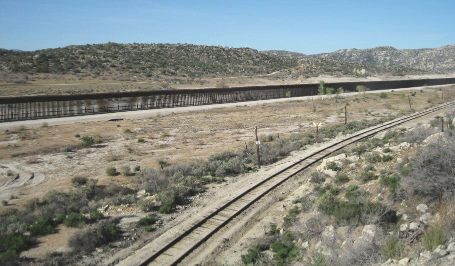 The border wall between the U.S. And Mexico across an arid landscape.