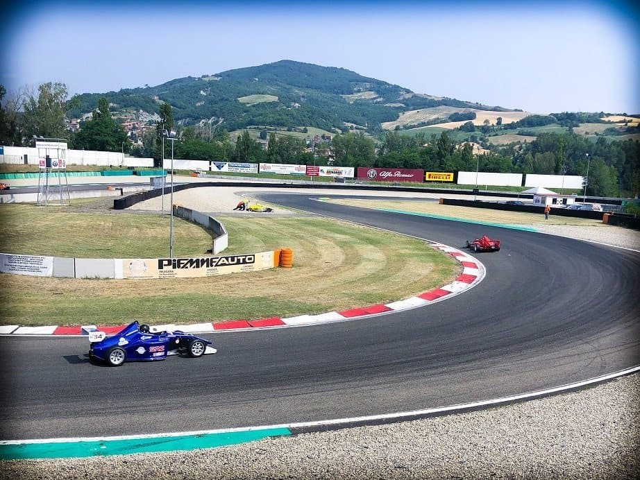 A blue race car, and a red race car ahead in the distance, racing on a car race track near Parma Italy
