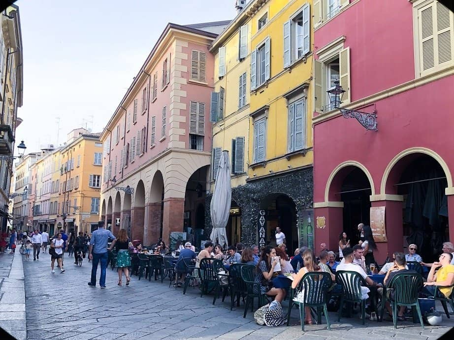 A street in the Centro Storico of Parma Italy. Brightly colored buildings in 17th century style architecture, with cafes on the sidewalk in front of the buildings.