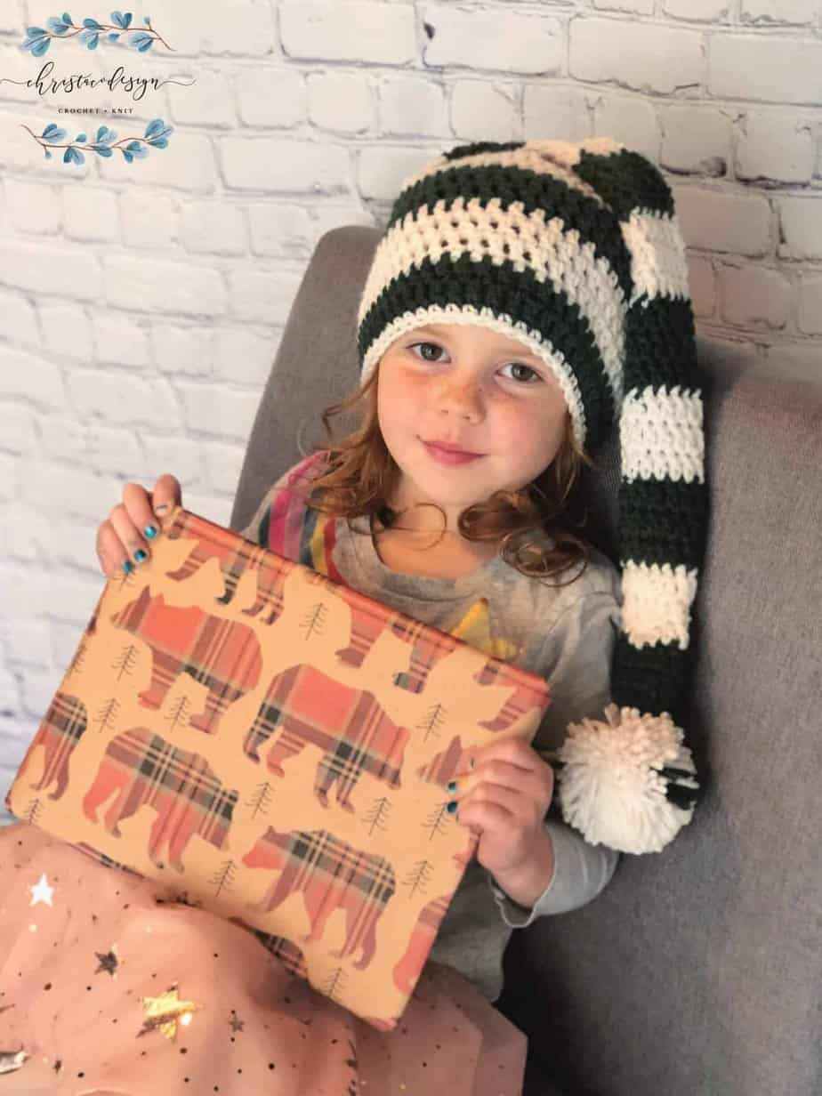 picture of girl with long striped stocking hat on in green and white holding a wrapped Christmas gift in bear paper