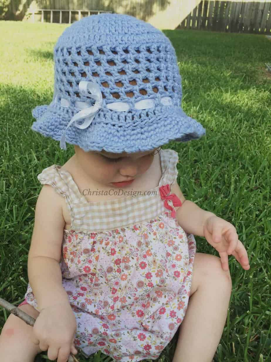 picture of girl in grass wearing crochet hat