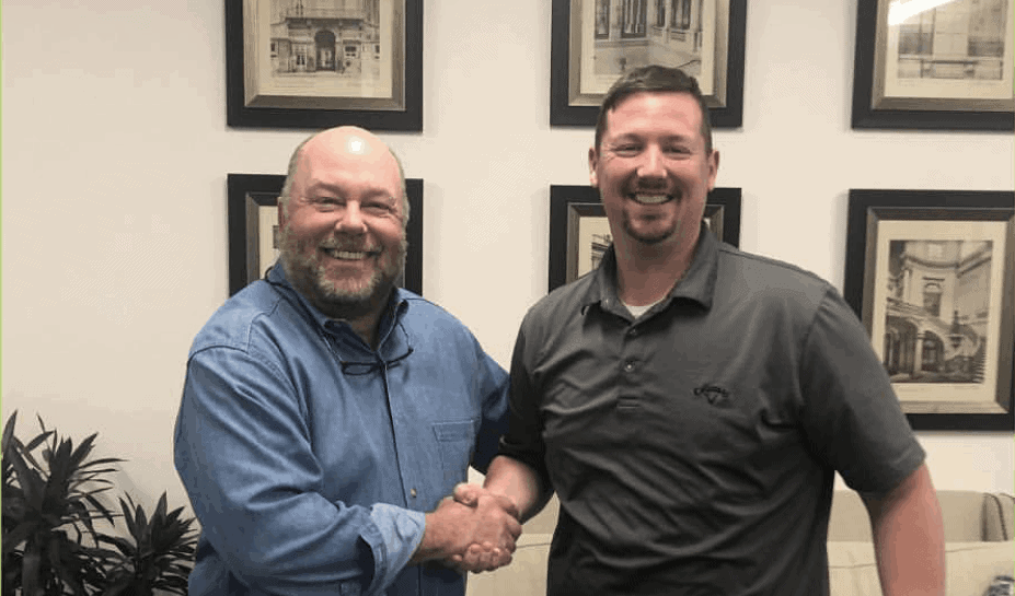 Pigtails & Crewcuts franchise owner Andrew McGehee shaking hands with CEO and President Wade Brannon