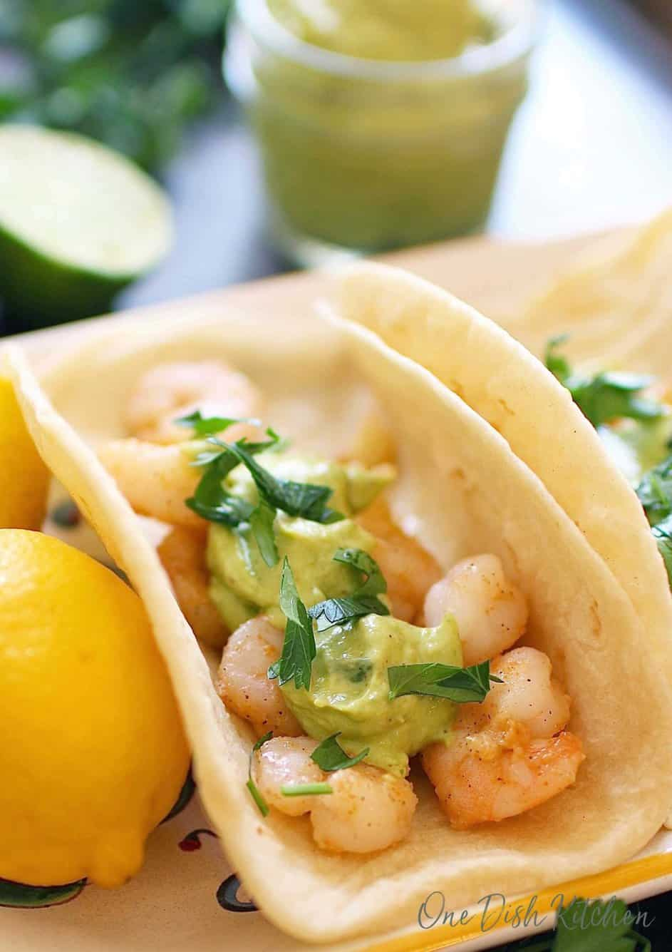 A shrimp taco topped with avocado sauce and cilantro on a plate next to a whole lemon and a jar of avocado puree in the background